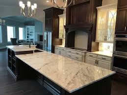 light color marble countertops kitchen island with sink cutout with dark cabinets and kitchen