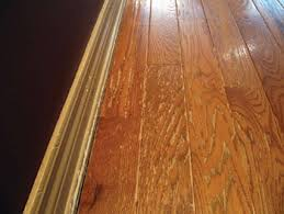 a prefinished solid wood floor and baseboard show damage caused by repeated use of a steam mop cleaner