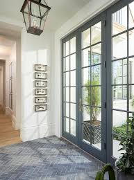 gray slate herringbone tiles lead to a a gray glass paned front door illuminated by a bronze carriage lantern while framed vintage keys in shadow boxes are