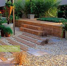 wooden planks laid in gravel form path going up steps to raised wooden deck with inset