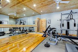 Rustic Home Gym with Ceiling fan, High ceiling, Hardwood floors, Carpet