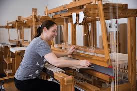 a weaver working on one of eakins handlooms which are built in sweden