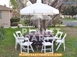 outdoor white patio umbrella with stand and round table with black tablecloth