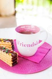 Tasse De Chocolat Chaud Avec Des Biscuits Au Chocolat Drôles Sur Un Placement Rose Avec Une Serviette Rose Une Citation Damitié Peinte Sur La