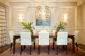 fabulously modern dining room pendant light fixture over a rectangle wooden table and white cushioned dining chairs decorated with twin wall sconces