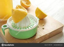 lemon squeezer on wooden board stock photo