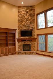 adorable corner fireplace design come with stacked stone fireplace and brown wooden mantelpiece with shelves and built in tv