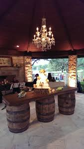 awesome wood table with drum legs and stone fireplace plus wine barrel chandelier also curved ceiling for patio design ideas