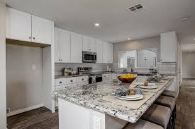 this gorgeous kitchen features j k cabinetry s white shaker cabinets with granite countertops the wood flooring and grayish tile backsplash are the perfect