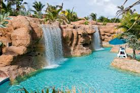 in ground pools with waterfalls. A Massive, Crystal Blue Pool With Multiple Artificial Waterfalls Tumbling Down From The High In Ground Pools