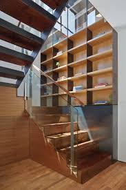 These stairs and bookcase use a variety of materials including glass, steel  and wood.