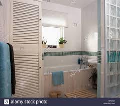 Louvre Türen Am Schrank In Modern Gefliestes Badezimmer Mit Glaswand