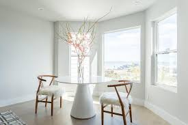 a dining room bay window is filled with a round white lacquered dining table lined with hans wegner wishbone chairs accented with sheepskin seats