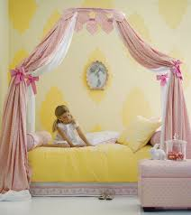 canopy bed with peach white long curtains tied with pink ribbon combined with yellow gray bedding set