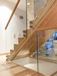 Large modern wooden glass railing staircase idea in Other