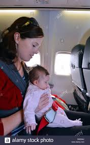 mother carry her infant baby during flight concept photo of air travel with baby