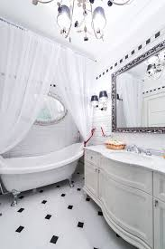 sheer shower curtains an antiqued silver mirror and elaborate chandelier hold their own against this clawfoot tub with polished metal fittings