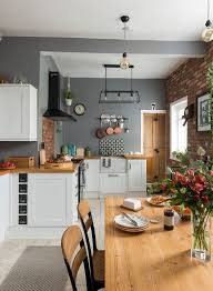 shaker style kitchen with grey walls a wooden dining table wooden worktops and industrial