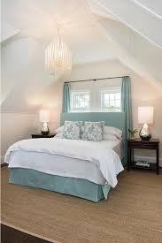 brown and blue bedroom features a vaulted ceiling accented with an arteriors tilda chandelier hangs over a blue headboard on bed dressed in a blue pleated