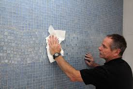 author tom meehan wipes the grout haze from a decorative glass tiled wall