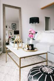 marble coffee table with brass base and flowers via the everygirl
