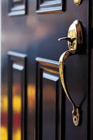 black four panel exterior door finished with a br door handle