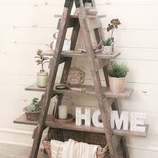 a sawhorse ladder bookcase with decorative items on it