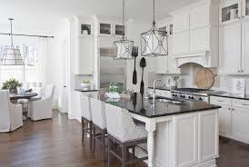 white kitchen island with black countertop and gray curved arm counter stools