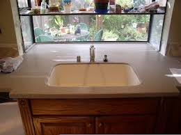 corian kitchen top:  it was more than the corian i really love the integrated sink not at all hard to keep clean here is a pic of the day it was installed  years ago