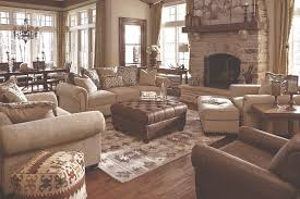 several neutral and rustic furniture peices in a living room with lots of wood and country