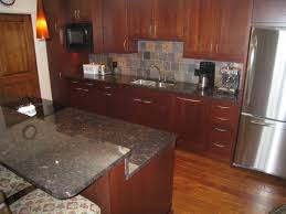 furniture dark brown wooden kitchen cabinet connected by grey tile backsplash connected by black granite