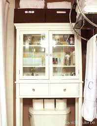 white wooden cabinet with glass door and drawers placed on the brown
