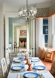 small rectangle dining table in front of wooden chairs under chandelier designer fountain lighting and white two door over laminate dining room flooring