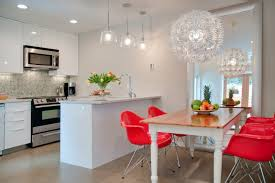 red chairs white chandelier big mirror wooden table fruits brown floor white kitchen cabinet built in