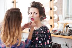 woman professional visagist doing makeup with pink lipstick to model stock image