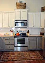 a kitchen with two tone painted cabinets that has parial overlay doors