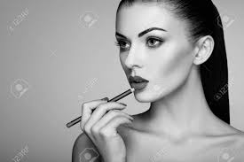 black and white photo of woman painting lipstick beautiful woman face makeup detail