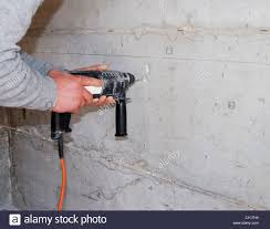 using electric drill. human hands using electric drill to make hole in concrete wall t