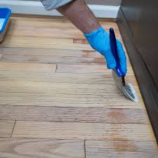 gloved hand applying sealer to hardwood floor along the room s edge with a brush