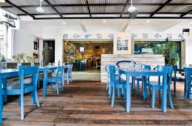 fascinating seafood restaurant decorating ideas with blue contemporary wooden dining table and chair set featuring rustic wooden flooring and black iron