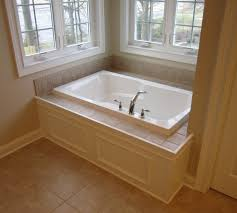 Master bathtub - Custom paneled front with tile tub deck.