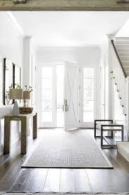 gray jute rug in front of white front door with x trim