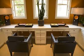 Double-work-station home office with built-in white desk and drawers looking