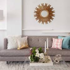 swoon worthy glam living room decor ideas white furry rug square coffee table vase flowers chandelier gray sofa blue white motif cushions white paint wall