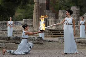 flame lighting olympics. actress katerina lehou, right, as high priestess, lights the torch during lighting flame olympics s
