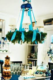 a usual chandelier covered with an evergreen wreath and turquouse ribbon