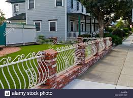 Interesting red brick and white painted wrought iron fence Stock