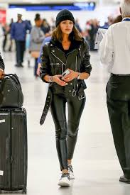 olivia culpo looks chic in a black leather jacket paired with matching leather tights and white