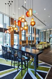 classy multi style and colors modern pendant lighting over long double pedestal dining table set on modern rugs as inspiring open floors interior decorating