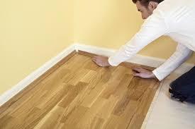 Man Holding Piece Of Quadrant On Laminate Flooring